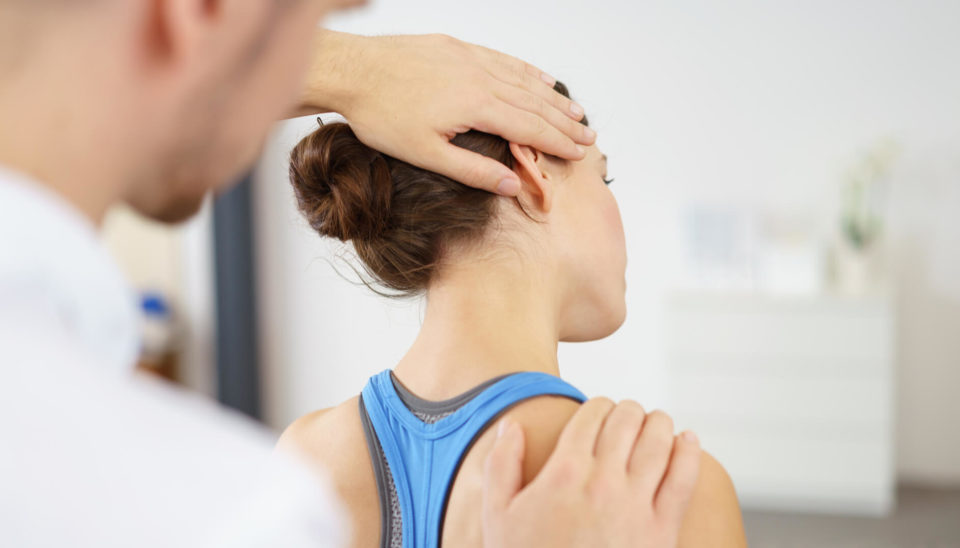 male-physical-therapist-stretching-the-injured-neck-of-a-female-patient-slowly-sportreat-services-physiotherapy