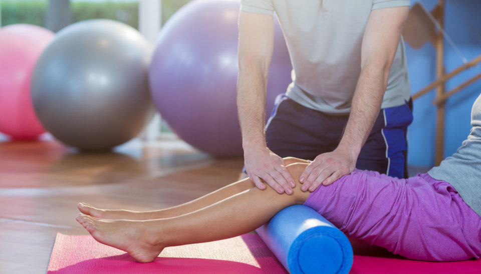 physiotherapist-assisting-woman-while-exercising-on-exercise-mat-in-clinic-sportreat-services-exercise-physiology